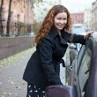 Stock Photo: Curly hair womopening car door