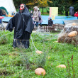 Scarecrow in black coat stands in middle of garden — Stock Photo #14903237