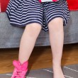 Small girl wearing pink shoes on leg sitting on sofa — Stock Photo