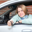 Blond woman holding car key in hands — Stock Photo