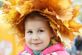 Child happy face with yellow maples — Stock Photo