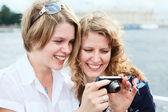 Due donne felici guardando schermo della macchina semplice a mano — Foto Stock