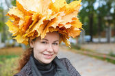 Attractive woman in autumn park with yellow maple — Stock Photo
