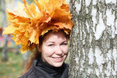 Young woman with maple standing near birch — Stock Photo