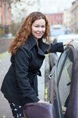 Happy smiling woman opeing car door — Stock Photo