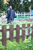 Scarecrow in black coat stands in the middle of the garden — Stock Photo