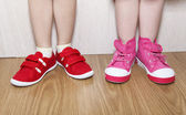 Children in wrong feet and right feet shoes wearing on legs — Stock Photo