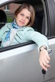 Woman sitting in land vehicle with car key — Stock Photo