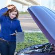 Broken vehicle with thinking womwith tablet computer near opened hood — Stock Photo #15857423