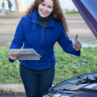 Woman showing thumb up standing in front of opened car cowling — Stock Photo
