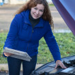 Stock Photo: Female driver with touchpad repairing car with opened engine hood