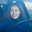 Royalty-Free Stock Photo: Young woman in car preparing to driving correcting back mirror