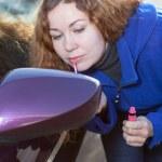Woman applying make up near car back side mirror — Stock Photo