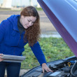 Stock Photo: Womdriver with touchpad repairing broken car with opened engine hood