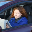 Young woman with touchpad sitting in car on driver seat — Stock Photo #15857469
