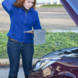 Stock Photo: Thinking curly hair womwith opened car cowling and tablet pc in hands