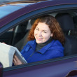 Young womwith touchpad smiling in car on driver seat — Stockfoto #15857561