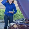 Woman in thought standing near car with tablet pc — Stock Photo
