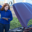 Stock Photo: Thinking womwith opened car hood and tablet pc
