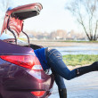 Woman's legs sticking out of a trunk — Stock Photo