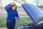 Broken vehicle with thinking woman with tablet computer near opened hood — Stock Photo