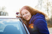 радостная девочка обнимает автомобилей и глядя на камеру в лучам солнца — Стоковое фото