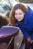 вьющиеся волосы женщина полюбоваться себя в зеркале автомобиля сзади против sunlights — Стоковое фото