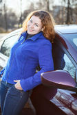 Joyful woman leaned to car smiling and looking at camera — Stock Photo