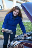 Female driver with touchpad repairing car with opened engine hood — Stock Photo