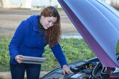 Woman a driver with touchpad repairing broken car with opened engine hood — Stock Photo