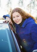 кудрявая девушка в синее пальто с автомобилем, глядя на камеру — Стоковое фото