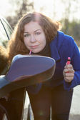 Woman applying make up near car back side mirror against sun rays — Stock Photo