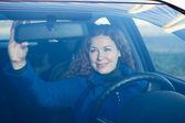 Mooie vrouw bij de voorbereiding van de auto naar drijvende corrigeren terug spiegel — Stockfoto