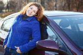 красивая женщина наклонилась к машине улыбается и смотрит на камеру — Стоковое фото