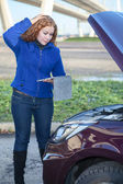 Thinking curly hair woman with opened car cowling and tablet pc in hands — Stock Photo