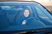 Attractive driver inside of car smiling through the windshield — Stock Photo