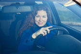 Smiling young woman the driver looking through car windglass — Stock Photo