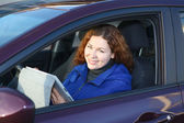 Young woman with touchpad smiling in car on driver seat — Stock Photo