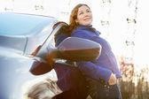 Chica alegre se inclinó contra el pie del coche en las luces del sol — Foto de Stock