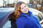 Joyful curly hair woman leaned against car and smiling — Stock Photo