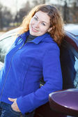 Happy young woman in blue coat standing near car and smiling — Stock Photo