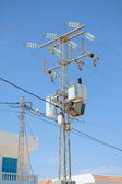 Transformers of an electrical post with powerlines against bright blue sky — Stock Photo