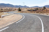 Asphalt way with white road marking in mountain terrain of Africa — Stock Photo