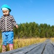 Caucasian small child walking on wooden plaks in swamp — Stock Photo