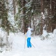 Young woman on ski looking back when skiing in winter forest — Stock Photo #18881485
