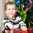 Small boy portrait with gifts near Christmas tree — Stock Photo