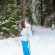Happy young skier with ski poles in hands up in winter forest — Stock Photo