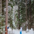 Happy young woman standing on ski in deep winter forest — Stock Photo