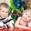 Foto Stock: Brother and sister with presents sitting near Christmas tree