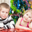 Brother and sister with presents sitting near Christmas tree — Stockfoto
